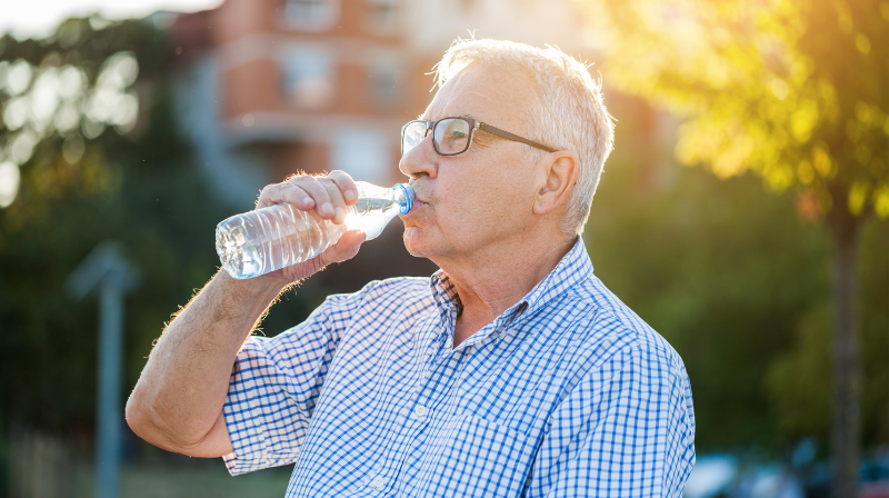 Senior man drinks water to avoid heat illness